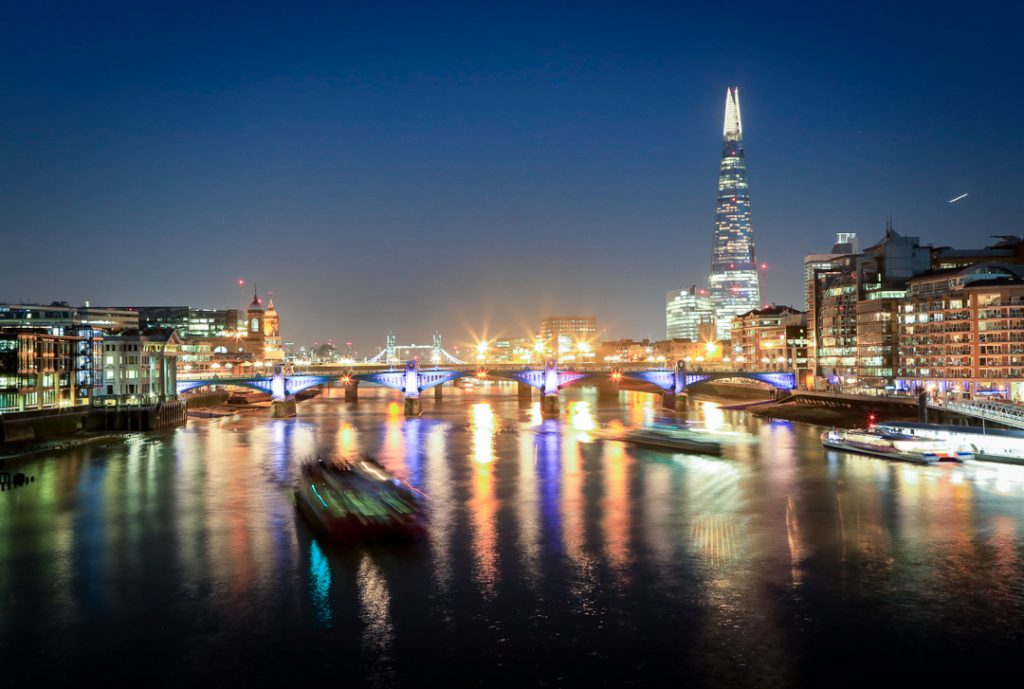 River Thames and The Shard at night with London Bridge and Tower Bridge.