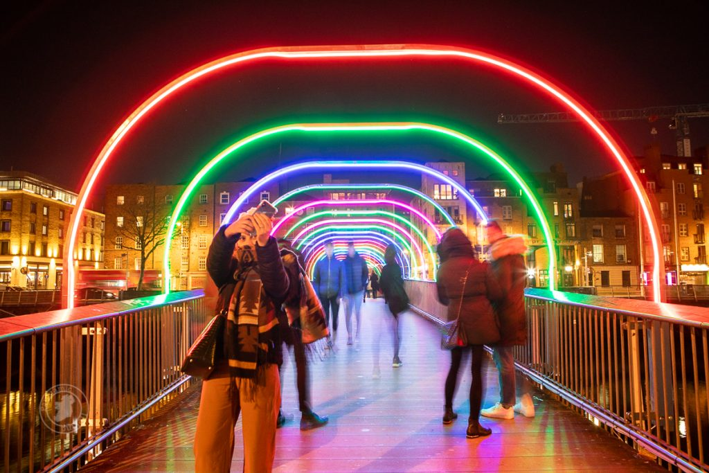 Woman takes selfie on Dublin's Millennium Bridge as part of Winter Lights Dublin