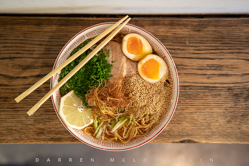 Bowl of noodles with eggs, pork, lemon and chopsticks.